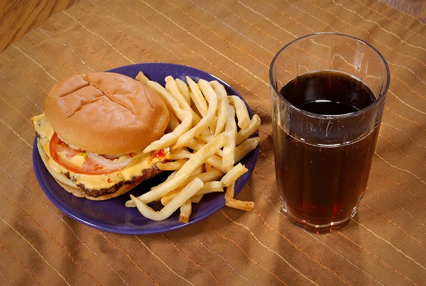 Cheeseburger with fries and a sugary drink